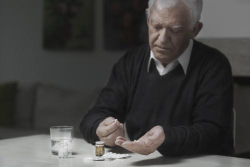 hombre mayor tomando analgésicos