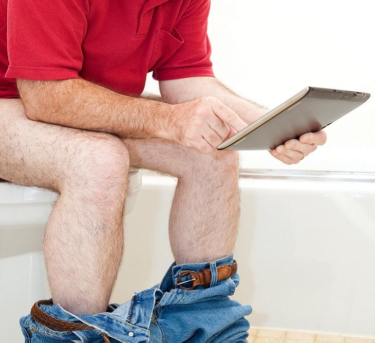 hombre con tablet en el baño