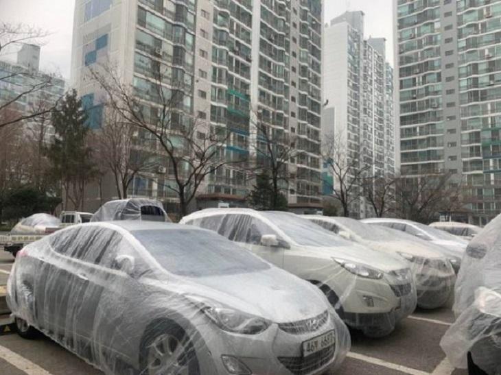 2. Un complejo de apartamentos donde los pintores envuelven los automóviles en láminas de plástico cuando se pinta para evitar salpicaduras