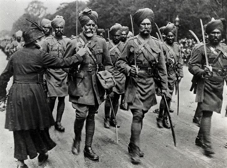 2. Una mujer francesa atando flores a los uniformes de los soldados del ejército británico-indio que asistieron a los combates en Francia - 1916.