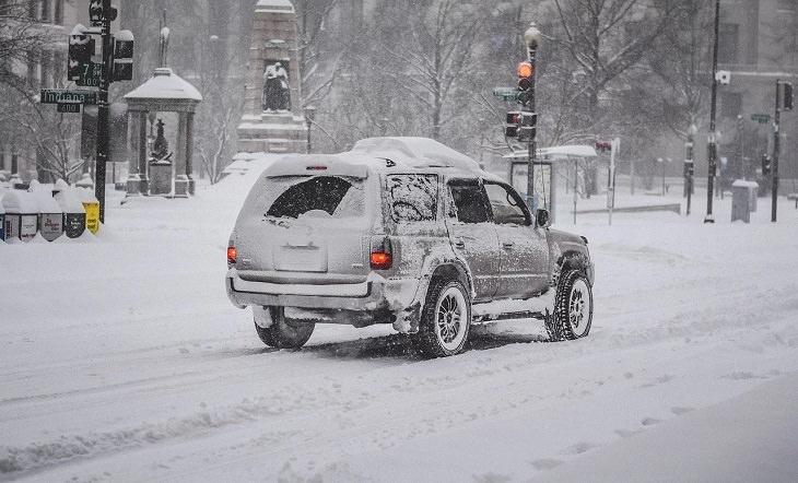 trucos útiles para la vida invernal Con un presupuesto para lidiar con hielo, escarcha y nieve, un automóvil cubierto de nieve en la carretera