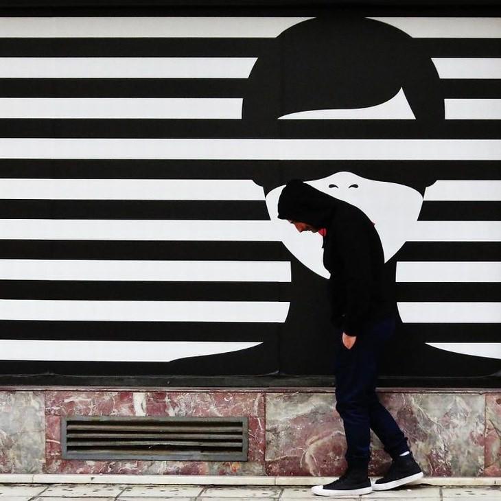 Fotógrafo Callejero chico paseando delante pintura