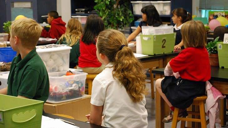 La Parábola de la manzana niños prestando atención en el salón de clases