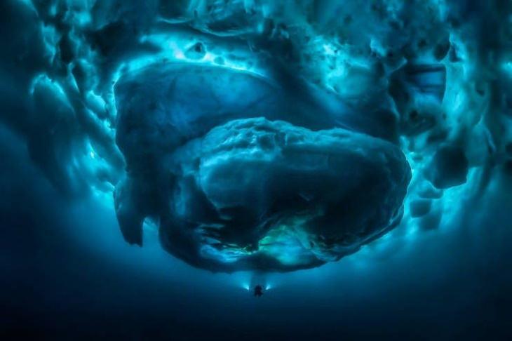 Un buzo comparado con el tamaño de la parte submarina de un iceberg