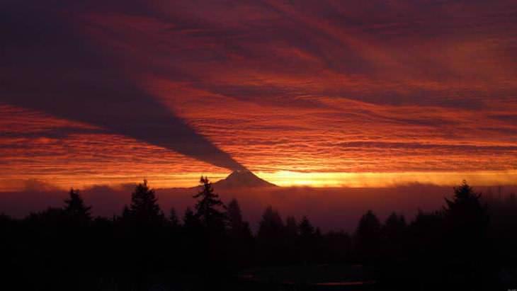 El monte Rainier proyectando sombras sobre las nubes