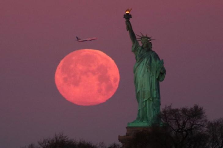 La creciente Luna de las Flores junto a la Estatua de la Libertad, Nueva York, EE. UU.