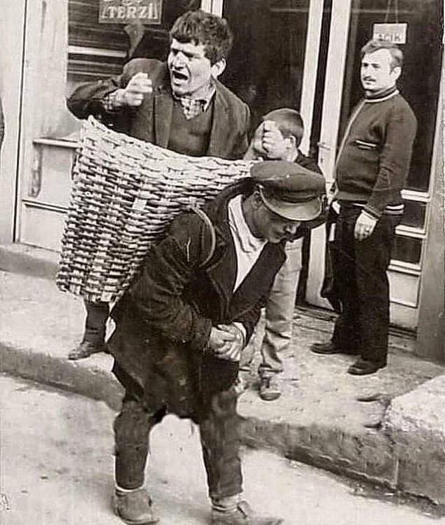 Un hombre intoxicado es llevado a casa por elhombre de la canasta quien era empleado en un bar en Turquía en la década de 1960