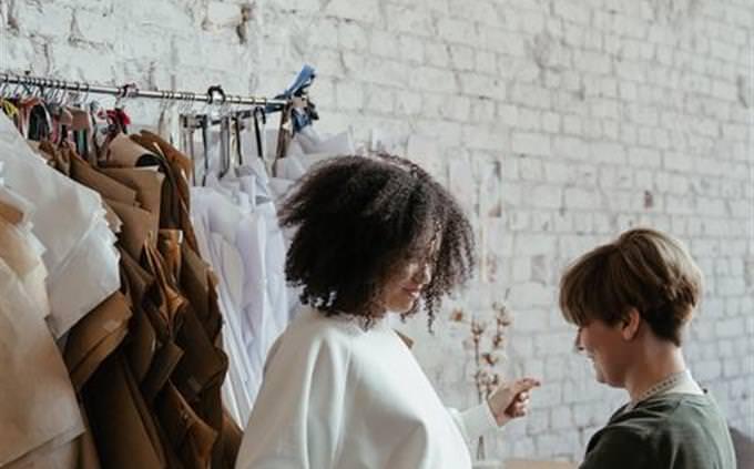 Mujer ajustando un vestido a otra chica