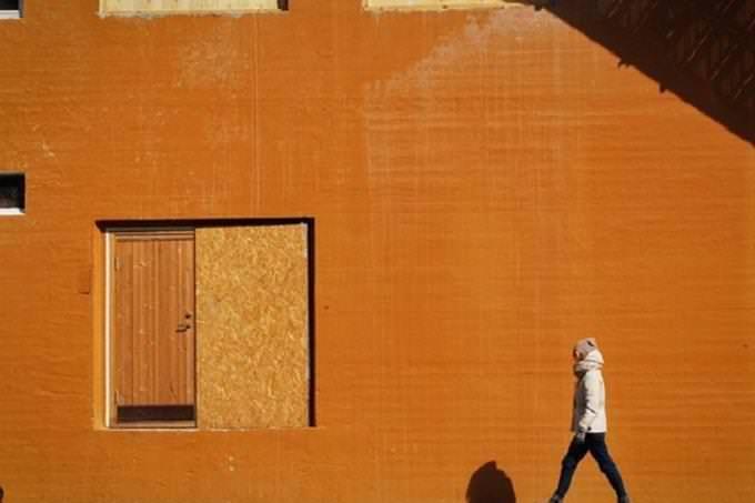 Hombre caminando cerca de puerta naranja