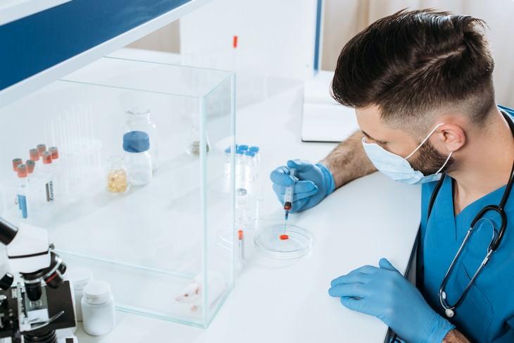 joven trabajando en un laboratorio covid-19