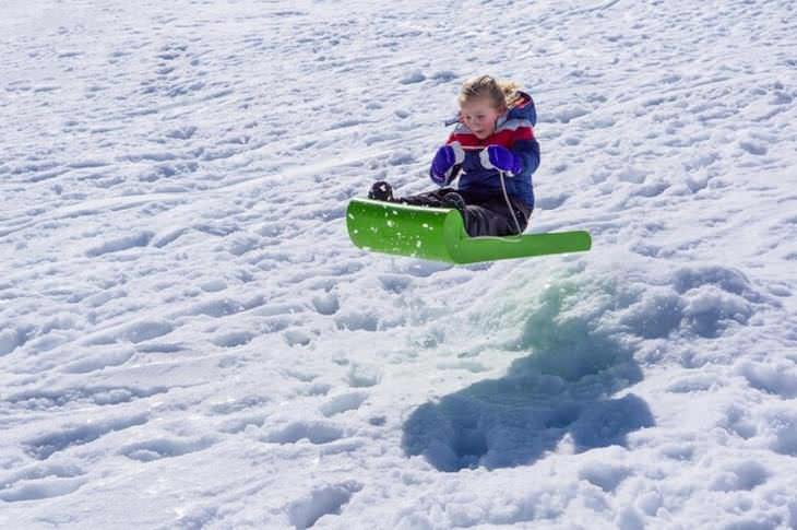 Fotos Que Reflejan Las Emociones Al Hacer Algo Por Primera Vez niño en trineo para nieve